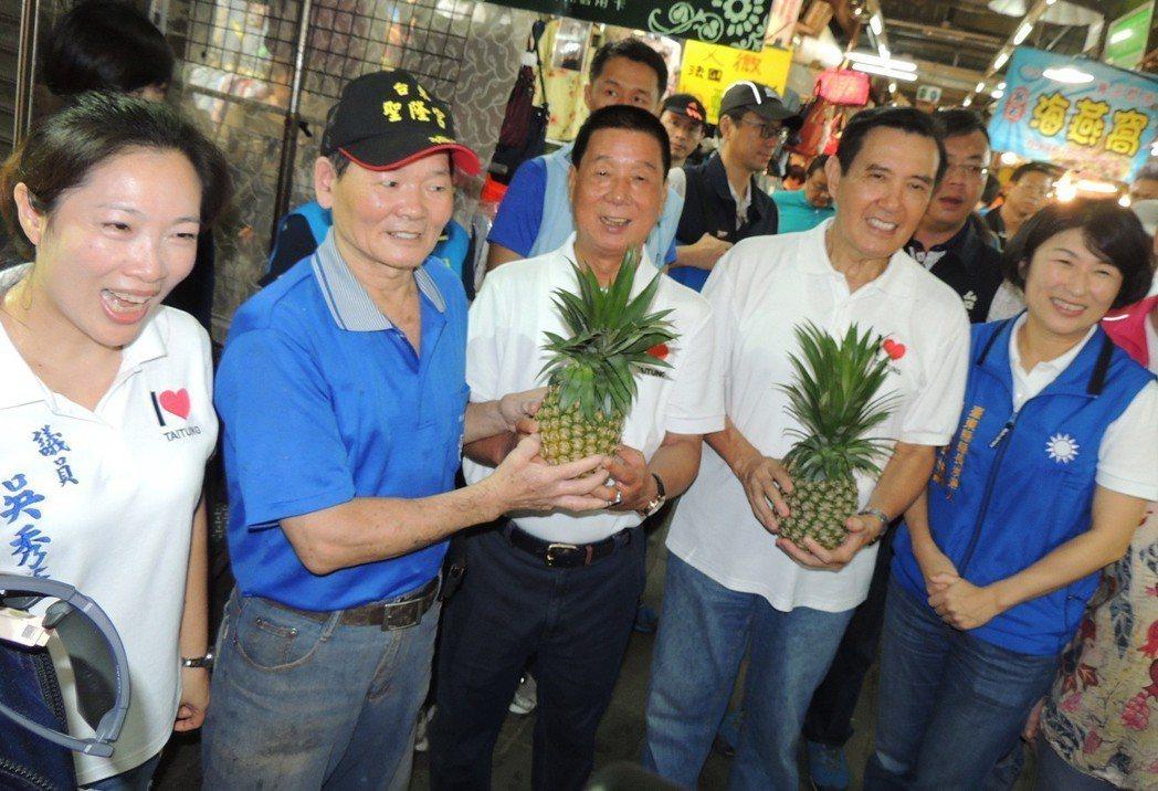 前總統馬英九(右二)陪台東縣長候選人饒慶鈴(右一)等人前往菜市場拜票,有水果商送...
