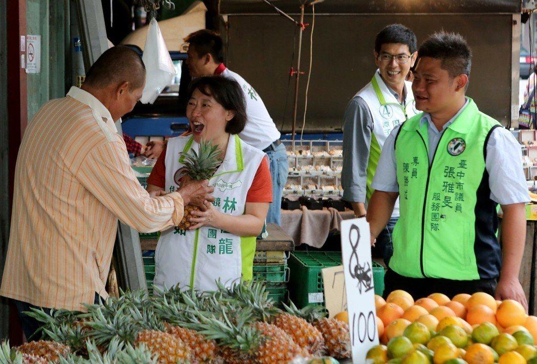 台中市長林佳龍的太太廖婉如(左二)扮起「母雞」角色,帶議員候選人在市場拜票。 圖...
