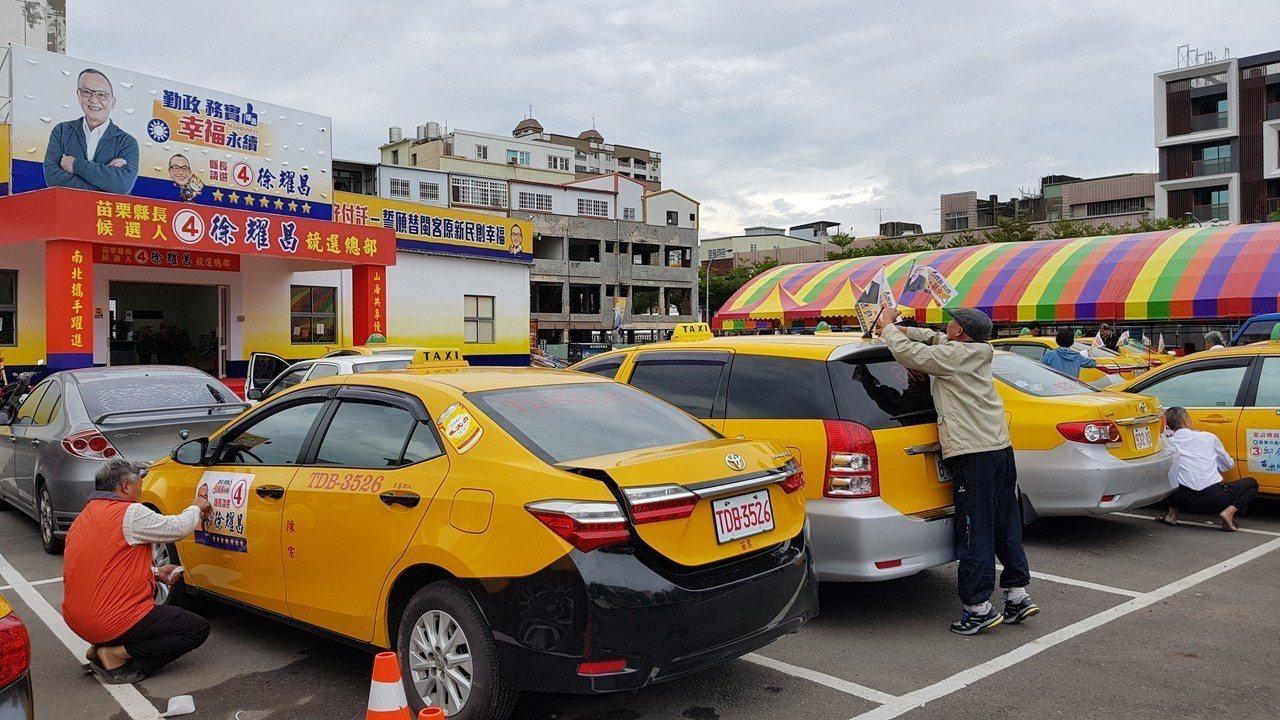 司機領到徐耀昌競選廣告與旗幟,紛紛在計程車張貼、裝設。記者黃瑞典/攝影