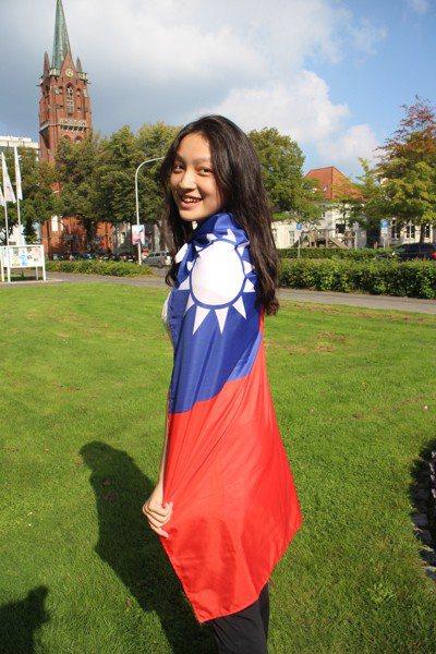 17歲的中山女高學生林語萱到德國做交換學生一年,開心地披上國旗留影紀念。圖/林語...