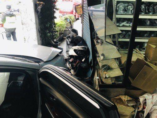 機車被夾在轎車與騎樓店家鐵門間扭曲變形,一旁店家的玻璃櫥窗也碎裂。記者巫鴻瑋/翻...