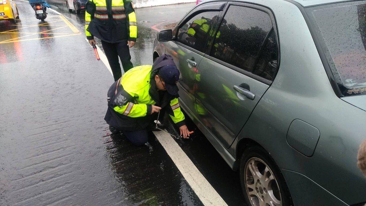 警方用千斤頂升高車底再設法拿出安全帽。記者鄭國樑/翻攝