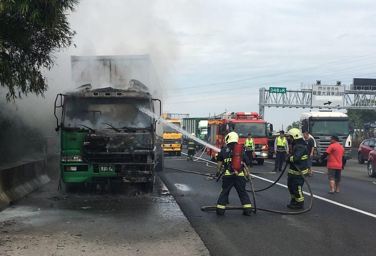 1輛貨櫃車今天在國道1號岡山路段起火,消防隊員正滅火。記者林保光/翻攝