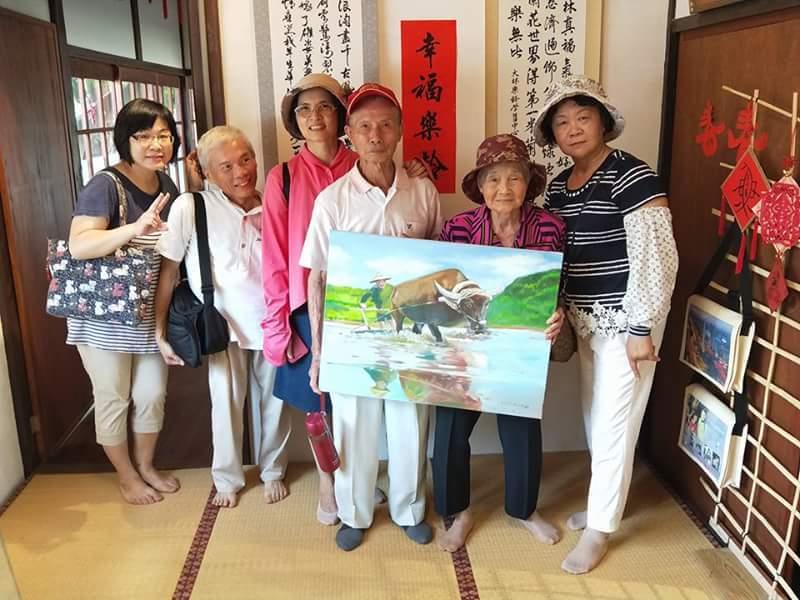 88歲的繪畫學員林午妹(右二)和親友們分享她的畫作 。圖/大林鎮公所提供