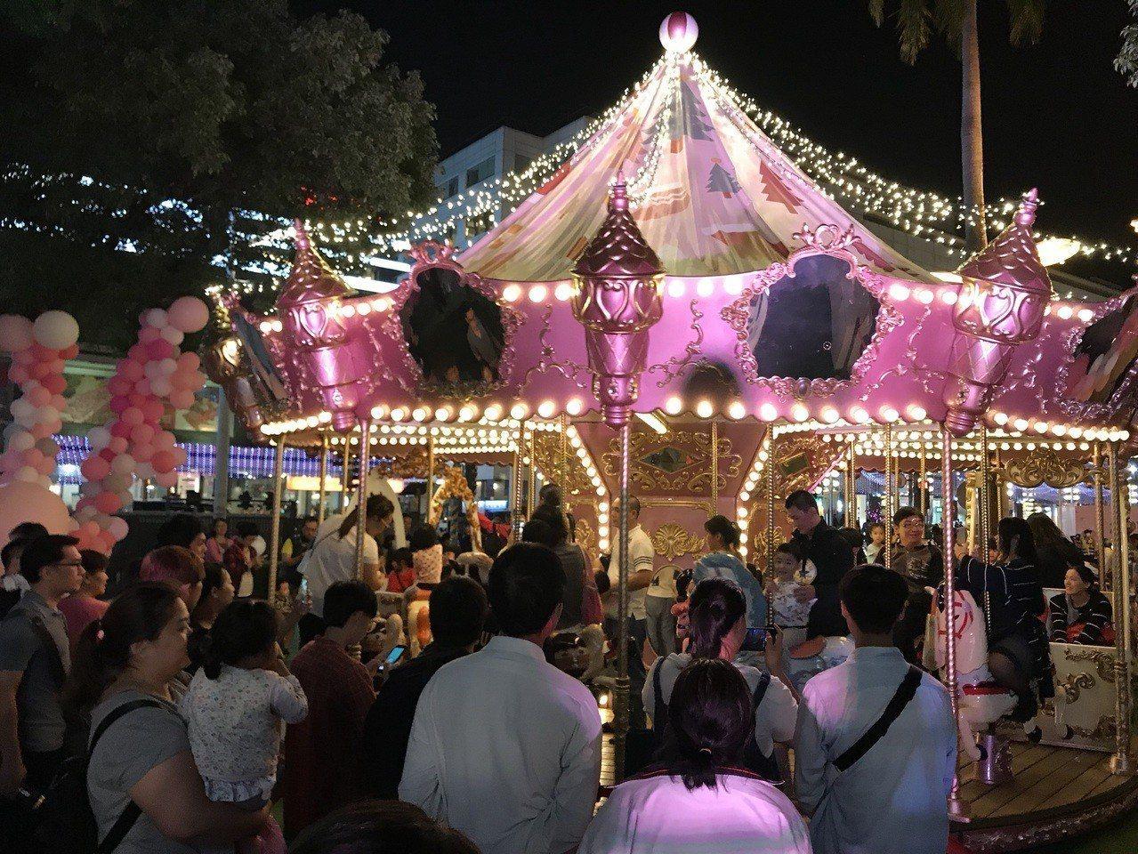 屏東聖誕節今晚點燈,百年公園變妝成「粉色聖誕」盛宴,吸引許多民眾到現場體驗粉紅盛...
