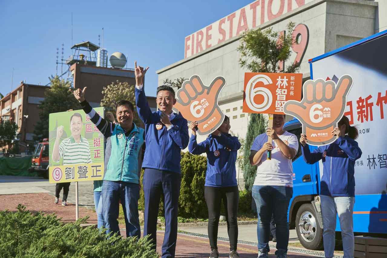 民進黨籍新竹市長候選人林智堅(左二)帶領市議員候選人劉聲正(左一)站在街頭揮手拜...