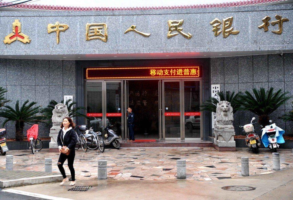 圖為一位女士從中國人民銀行松溪縣支行前經過。 中新社