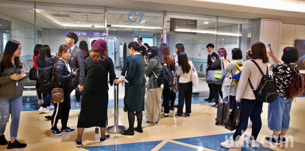 韓團「FTISLAND」中午抵台,管制區內還是有約30位粉絲在守候。記者鄭超文/...
