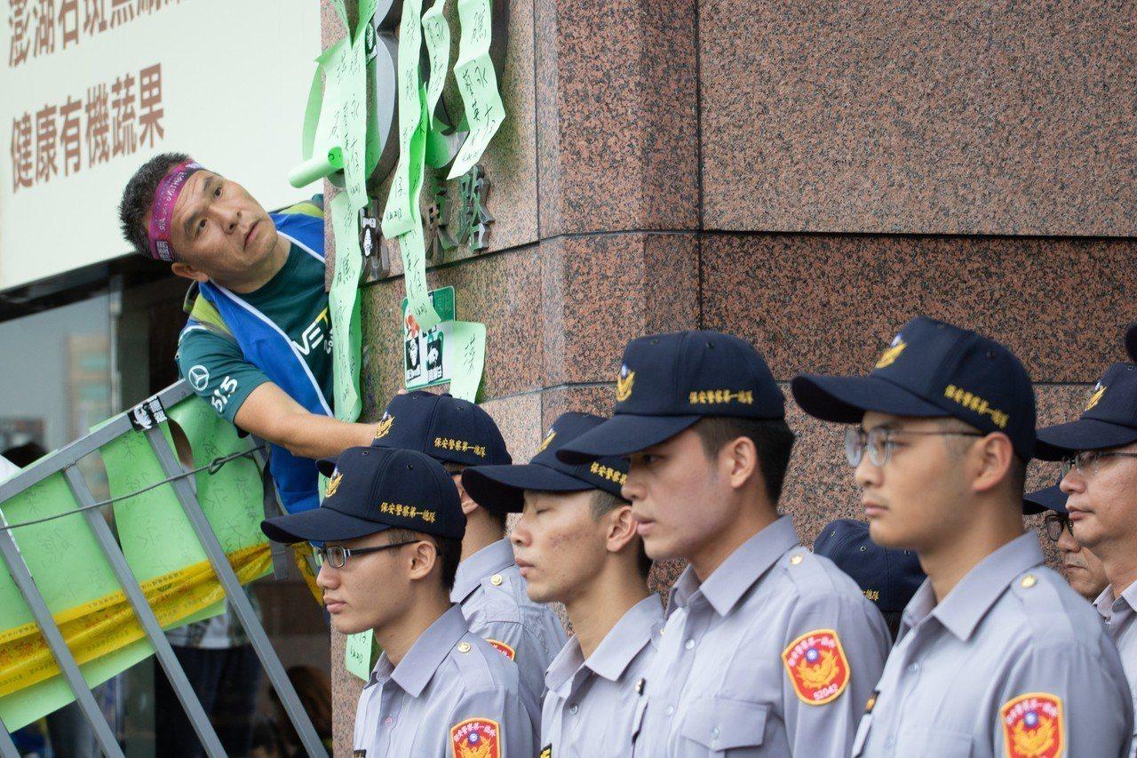 遊行民眾將寫有「藻礁永存」字樣的紙條貼在民進黨中央黨部外牆上。記者李隆揆/攝影