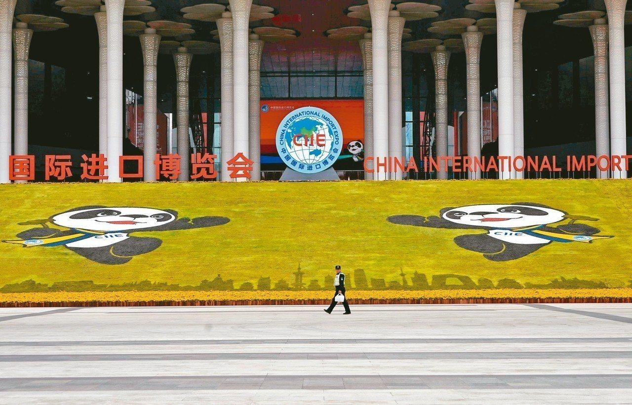 中國國際進口博覽會明登場,安全人員昨天行經會場前。 (路透)