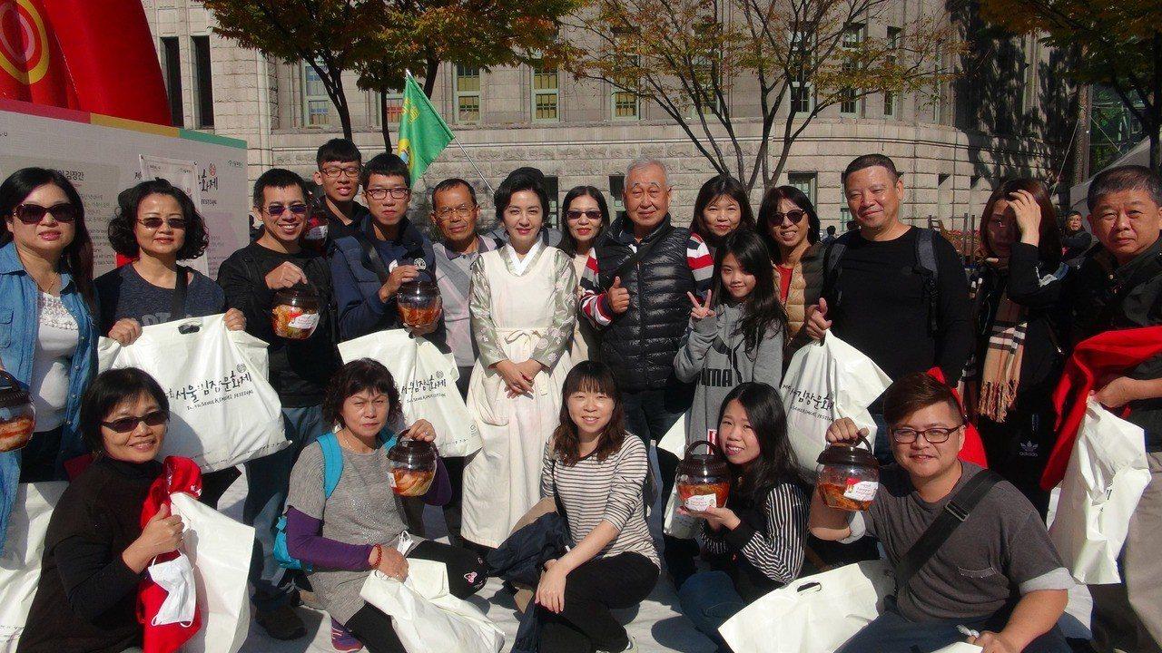 第5屆首爾越冬泡菜文化節在首爾廣場展開,泡菜研究家崔智雅(中)與台灣觀光客合影。...