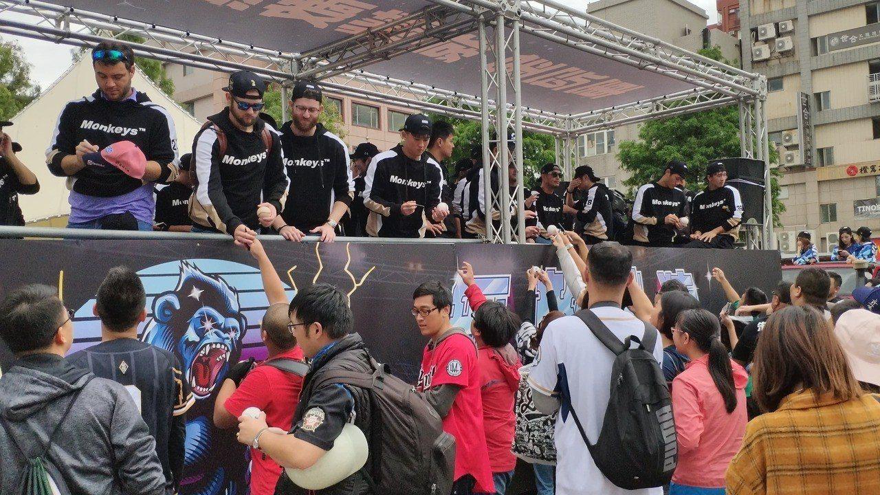 Lamigo桃猿隊球員搭乘桃猿大貨車與球迷互動、簽名。聯合報系記者李京昇/攝影
