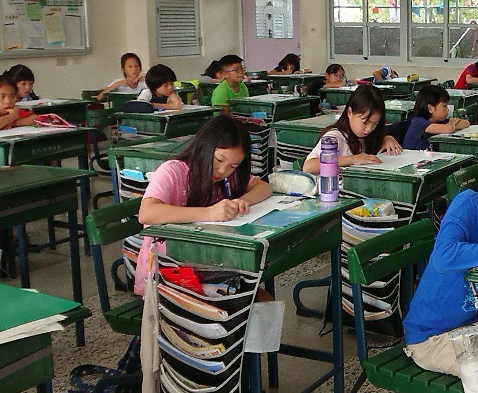聯合盃作文賽高雄區初賽登場,小小考生們在考場內振筆疾書。記者蔡容喬/攝影