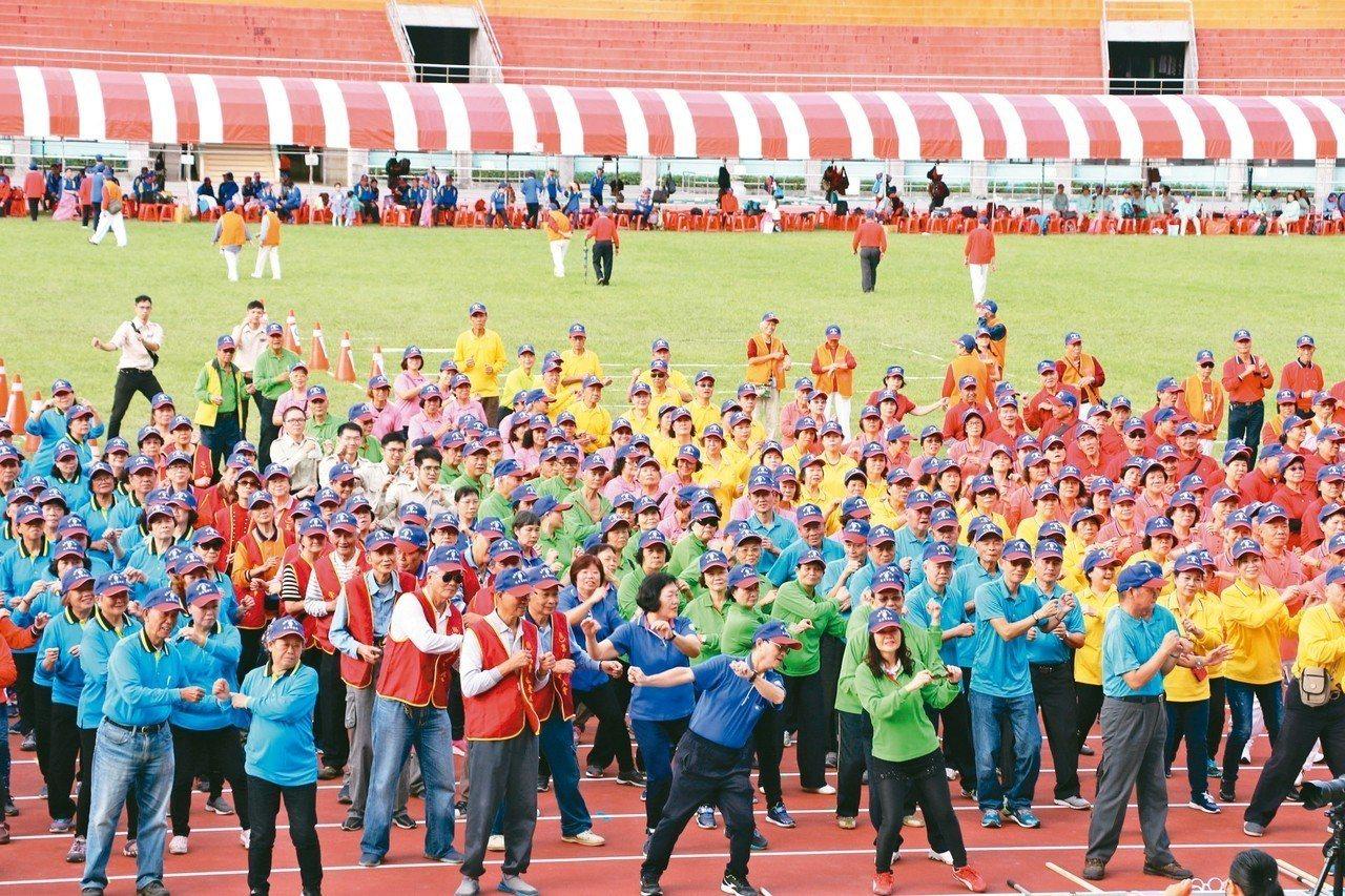 新北長青趣味運動大會昨在板橋第一運動場舉辦,開幕式上齊做健康操活動筋骨。 記者施...