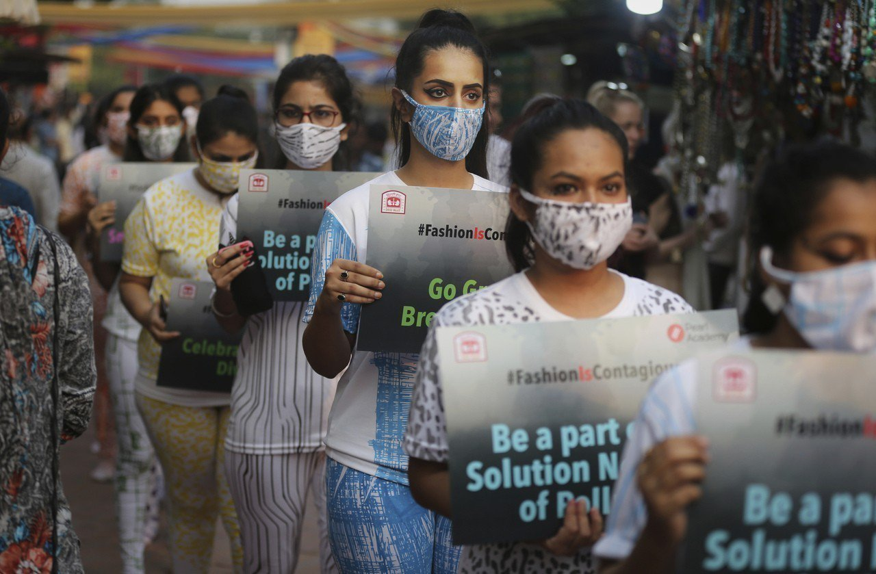 印度學生二日戴著口罩與手持標語,在新德里一處市場內遊行希望喚起人們重視空汙危機。...