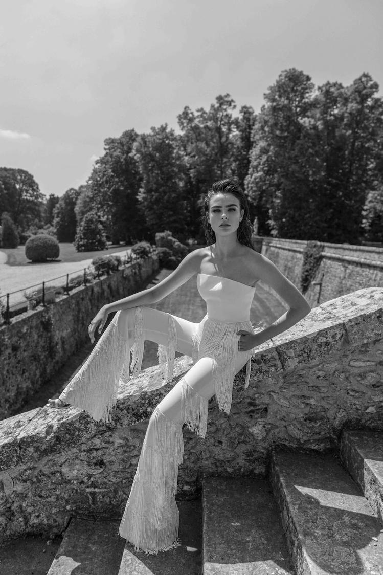 白色流蘇連身褲裝以進口珠鑽、閃片及獨特的時裝面料為基礎,搭配上百顆水鑽精巧地接合...