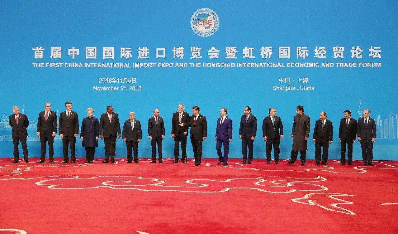 大陸國家主席習近平(中)昨在進博會開幕前,迎接各國領導人。 (中新社)