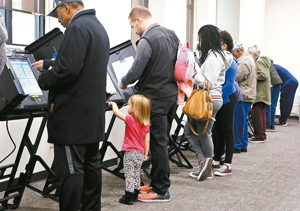 圖為美國民眾操作機器提前投票。 (美聯社)