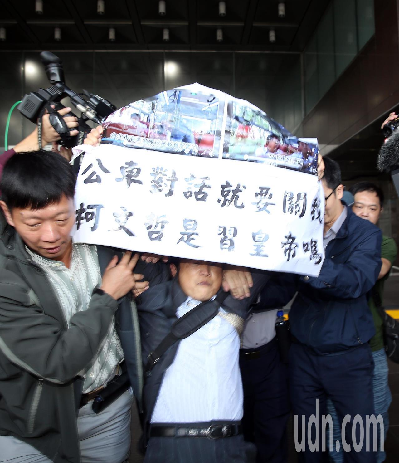 台北市長柯文哲上午遭抗議人士舉海報在身旁抗議,抗議者隨即被警方推出市政府外。記者...