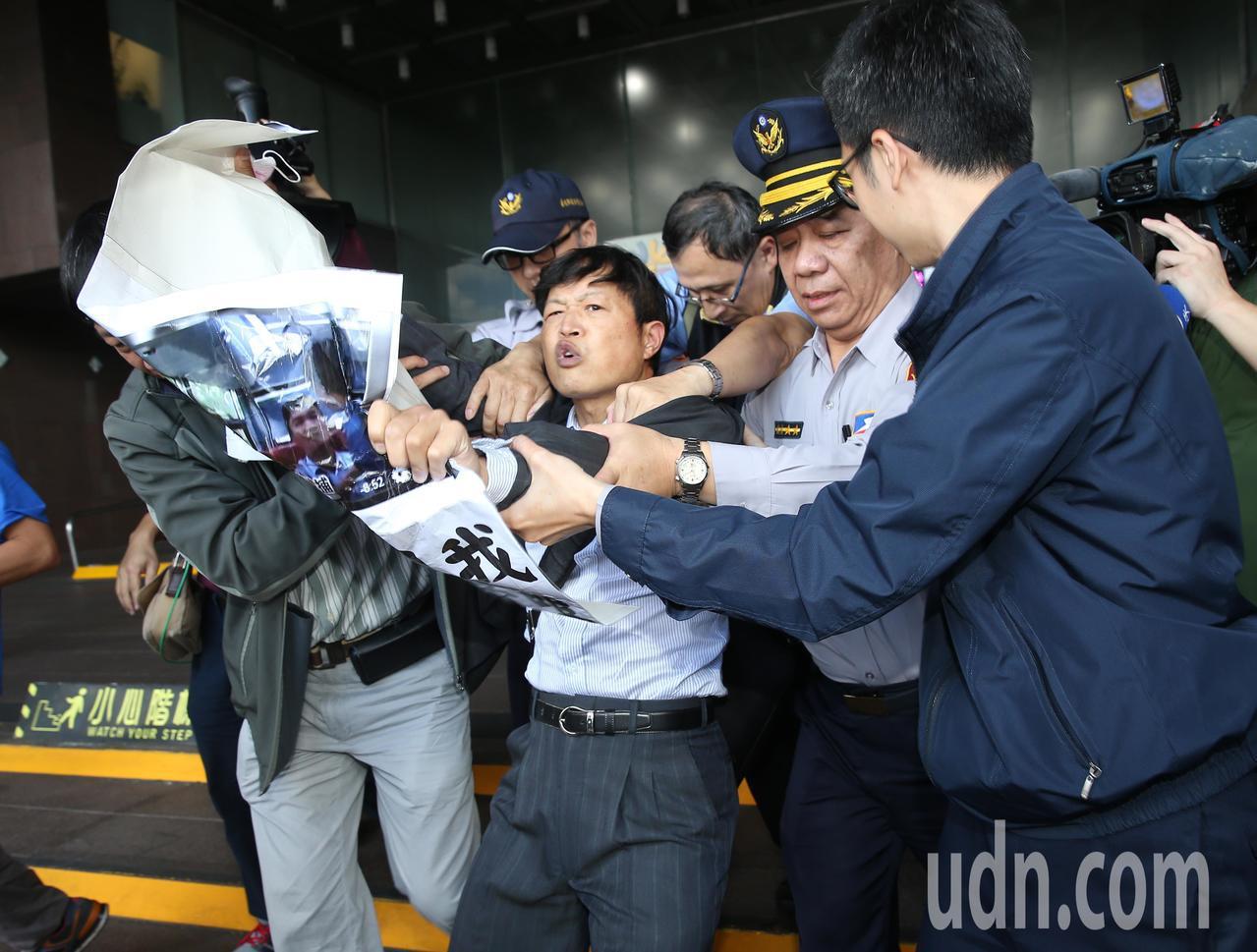 台北市長柯文哲上午出席活動,遭抗議人士舉海報在身旁抗議,抗議者隨即被警方推出市政...