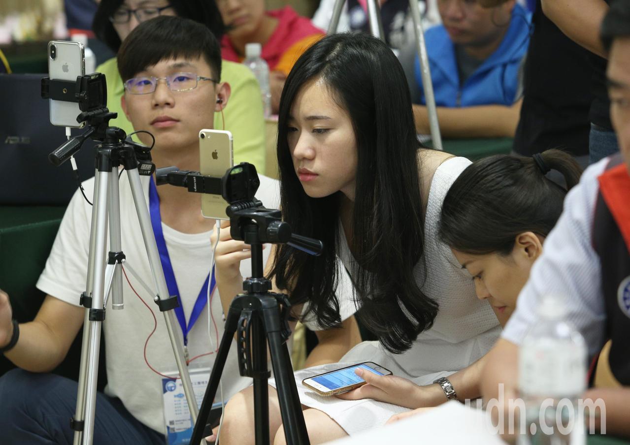 國民黨高雄市長參選人韓國瑜二女兒韓青(中),外型亮眼的韓青在記者會現場用手機進行...
