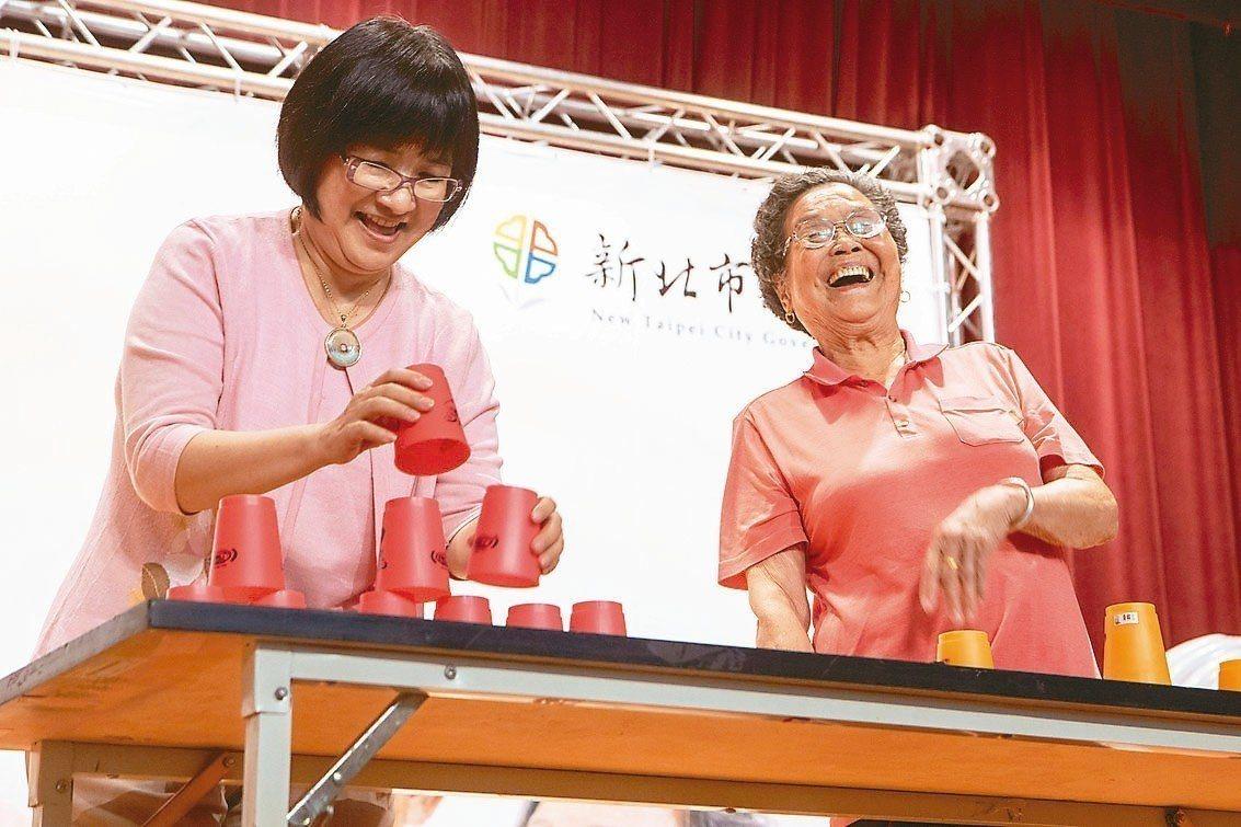 92歲黃賴月(右)是世界競技疊杯錦標賽第9名,疊杯速度讓一旁的社會局長張錦麗(左...