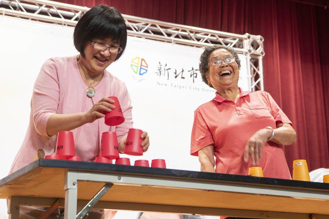 92歲黃賴月(右起)是世界競技疊杯錦標賽第9名,疊杯速度讓一旁的社會局長張錦麗完...
