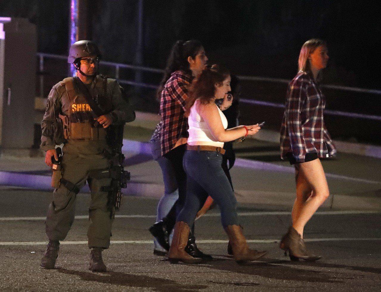 槍口餘生的目擊者在警方護送下離開現場。 歐新社