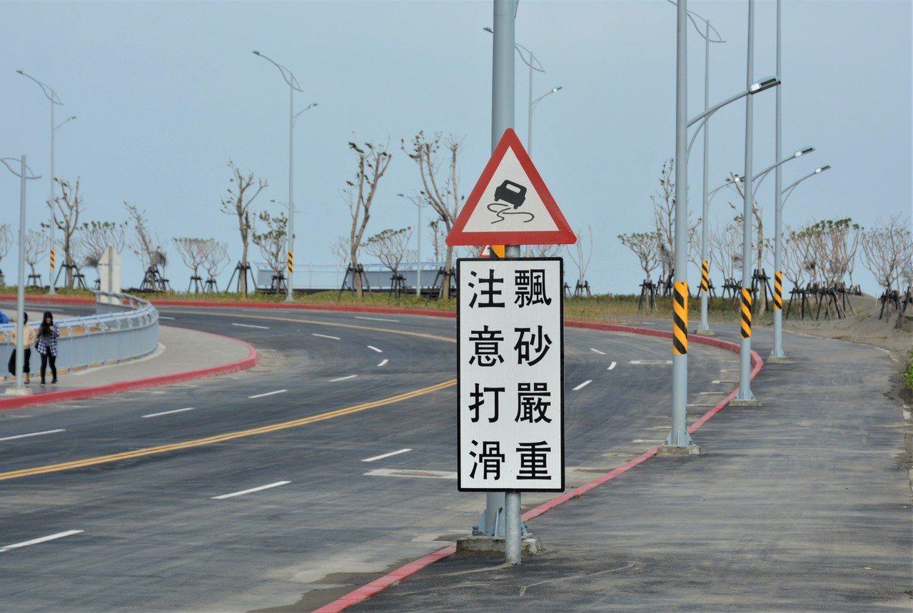 新竹市南寮大道9日竣工通車,路旁豎立警示標誌「飄砂嚴重,注意打滑」,民眾行車要減...