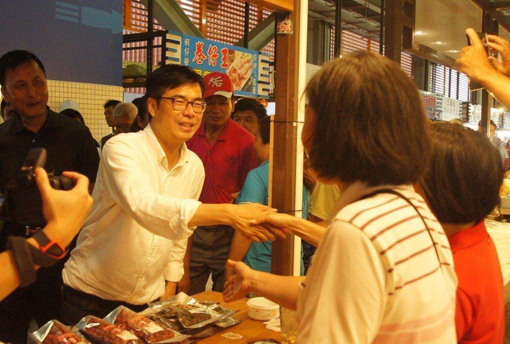 陳其邁(左)今天逛新落成的高雄市梓官「蚵仔寮魚貨直銷中心」,與攤商握手。記者林保...