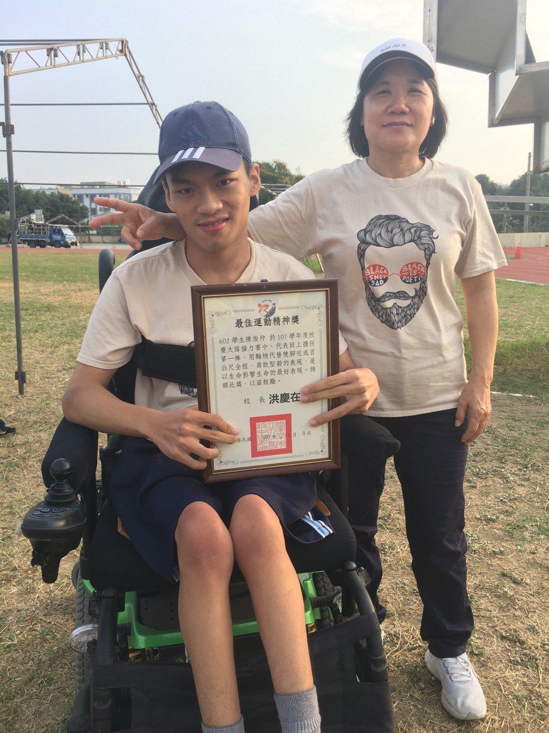 台南永仁高中三年級陳俊仲(左)用輪椅完成人生第一次參加大隊接力,校長洪慶在頒給他...