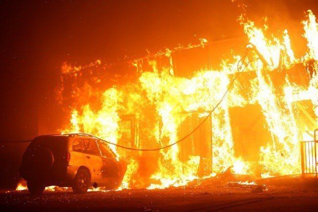 加州野火席捲天堂鎮,圖為當地民房及汽車陷入火海。路透