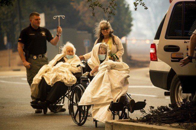 加州野火席捲天堂鎮,圖為救護人員撤出當地羽毛河醫院的病患。美聯社