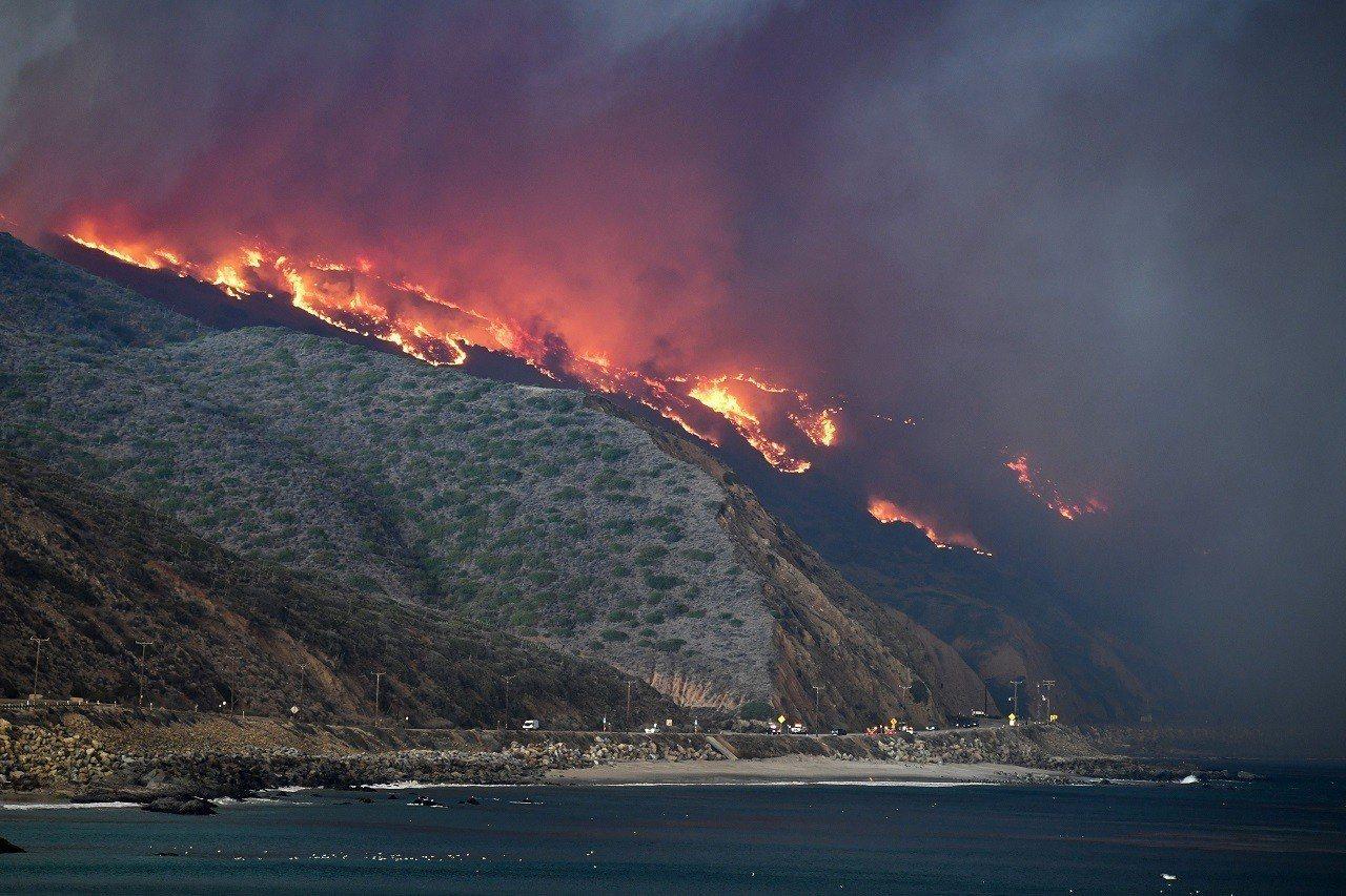 美國加州近日開始吹起強勁炙熱的沙漠風,助長「伍爾希」野火越過101號美國國道直奔...