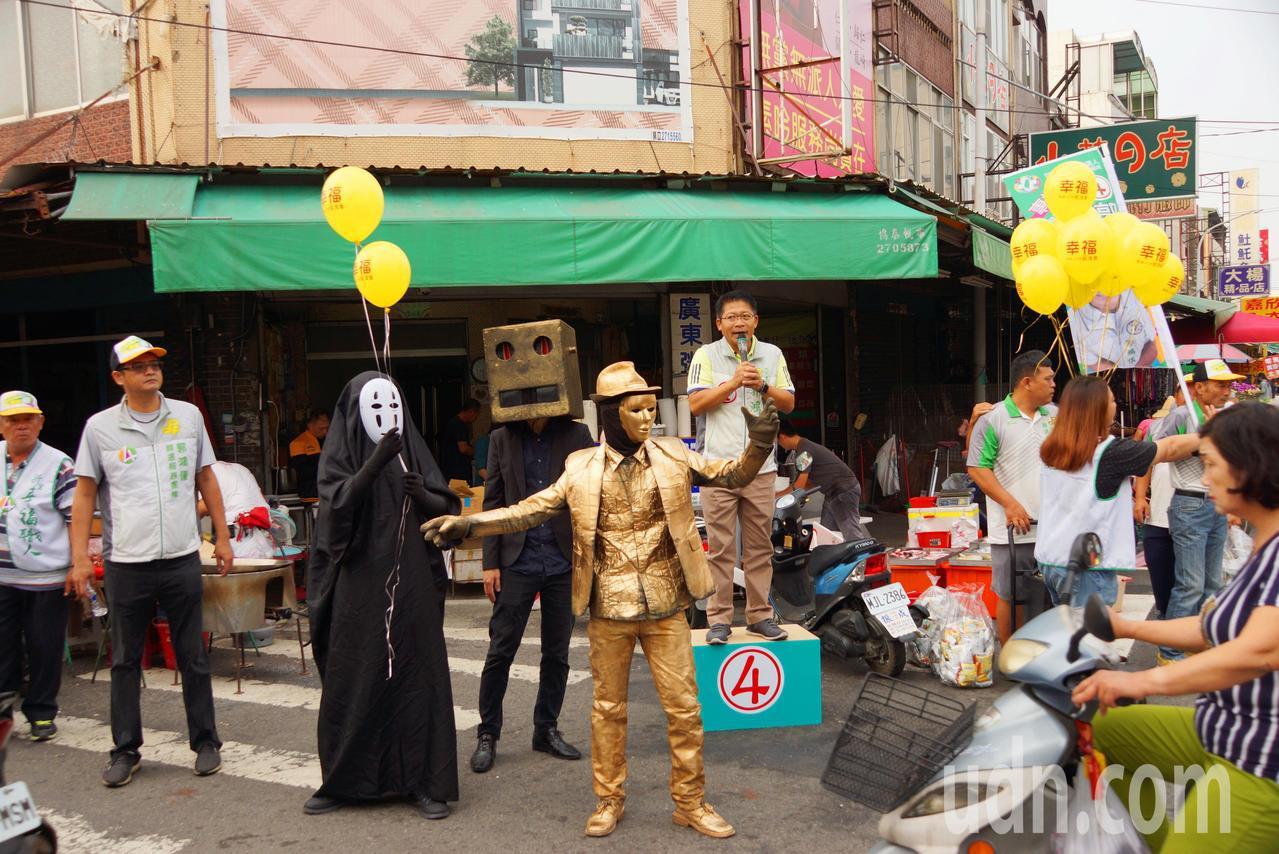 台南市議員候選人郭鴻儀今天請街頭藝術家「無臉男」等陪同到市場掃街。圖/郭鴻儀服務...