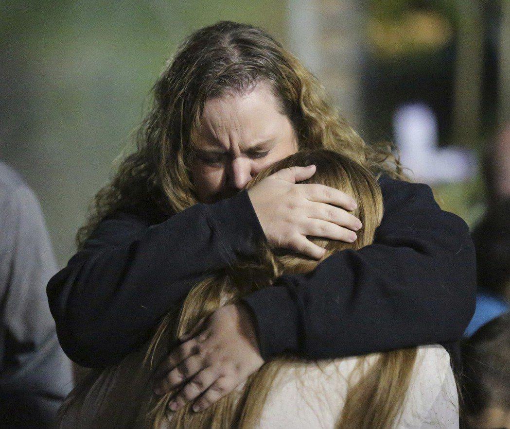 在千橡市槍擊案的哀悼儀式上,受害者與家人相擁。 (美聯社)