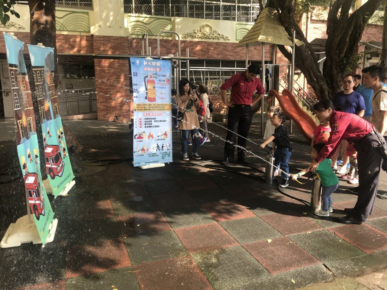 活動除有園遊會義賣外,北市消防局讓雙胞胎小朋友們充當消防員,以強力水柱模擬救火的...