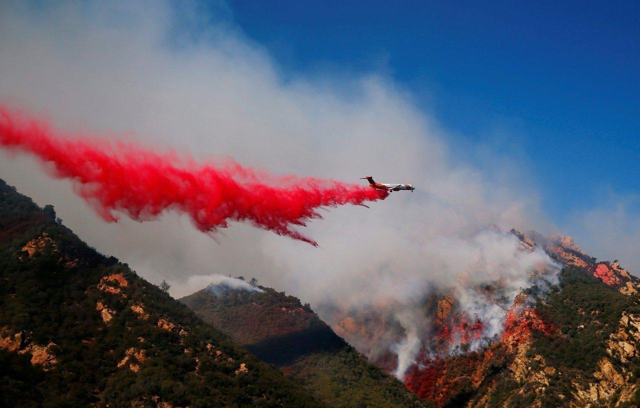 對抗加州伍爾西林火的消防員11日在空中投下阻燃劑。路透
