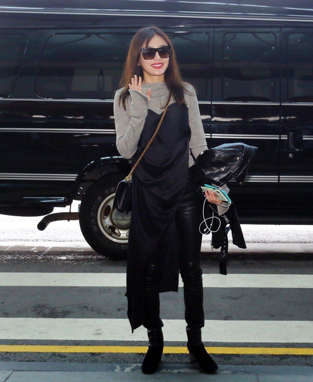 秦嵐以灰色長袖上衣搭黑色洋裝再內搭皮褲,洋裝側邊開高衩的設計讓這種多層次穿法不會...