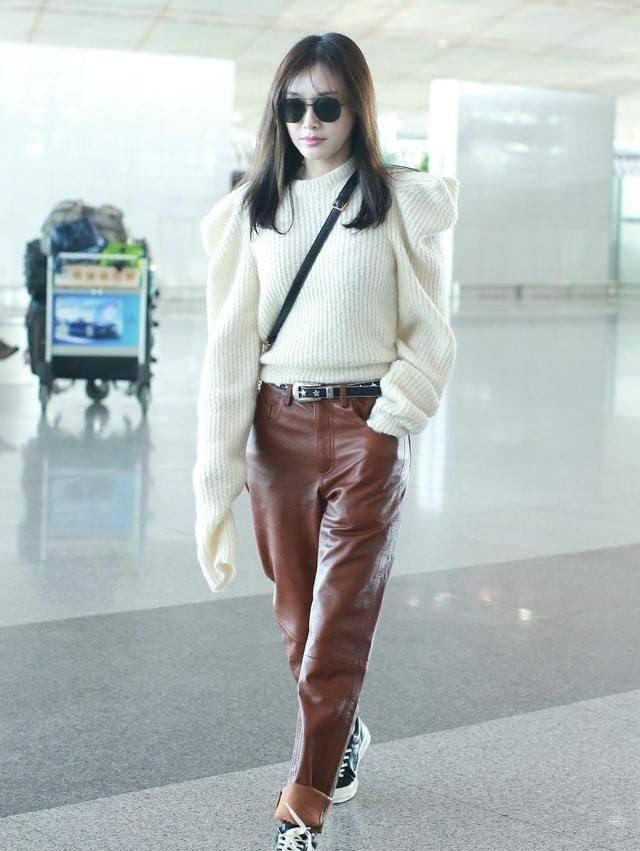 白色毛衣有特殊的肩線,搭配版型較寬鬆的棕色皮褲穿出秋冬的溫暖感,反摺的褲管透出小...