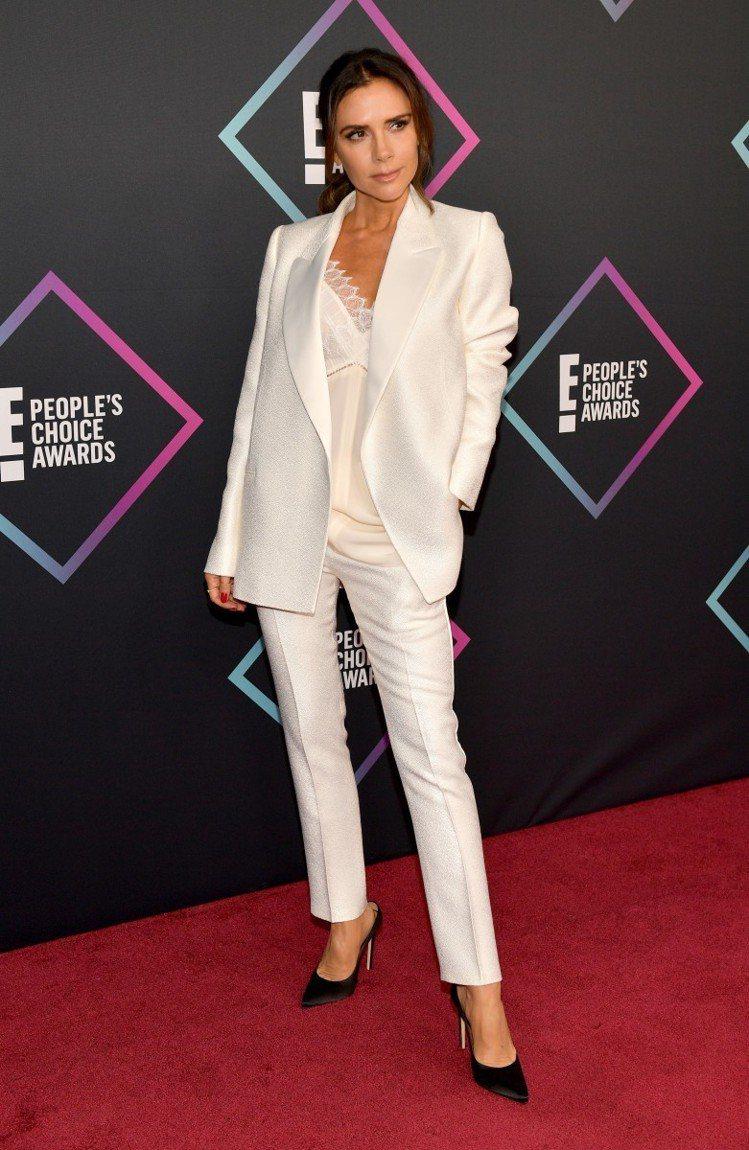 「貝嫂」維多利亞貝克漢穿自己的同名品牌白色西裝褲裝出席全美觀眾票選獎,內搭白色蕾...