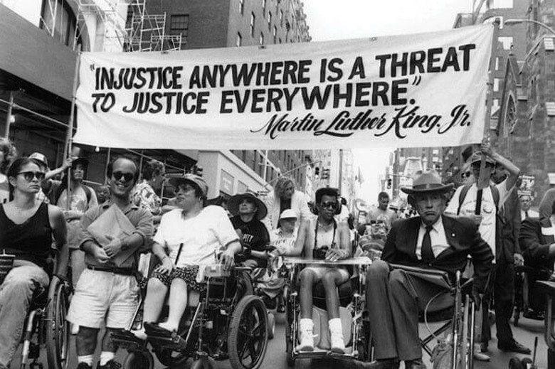 圖為1990年代美國身心障礙權利倡議者街頭遊行畫面。遊行者大多為輪椅使用者,布條...