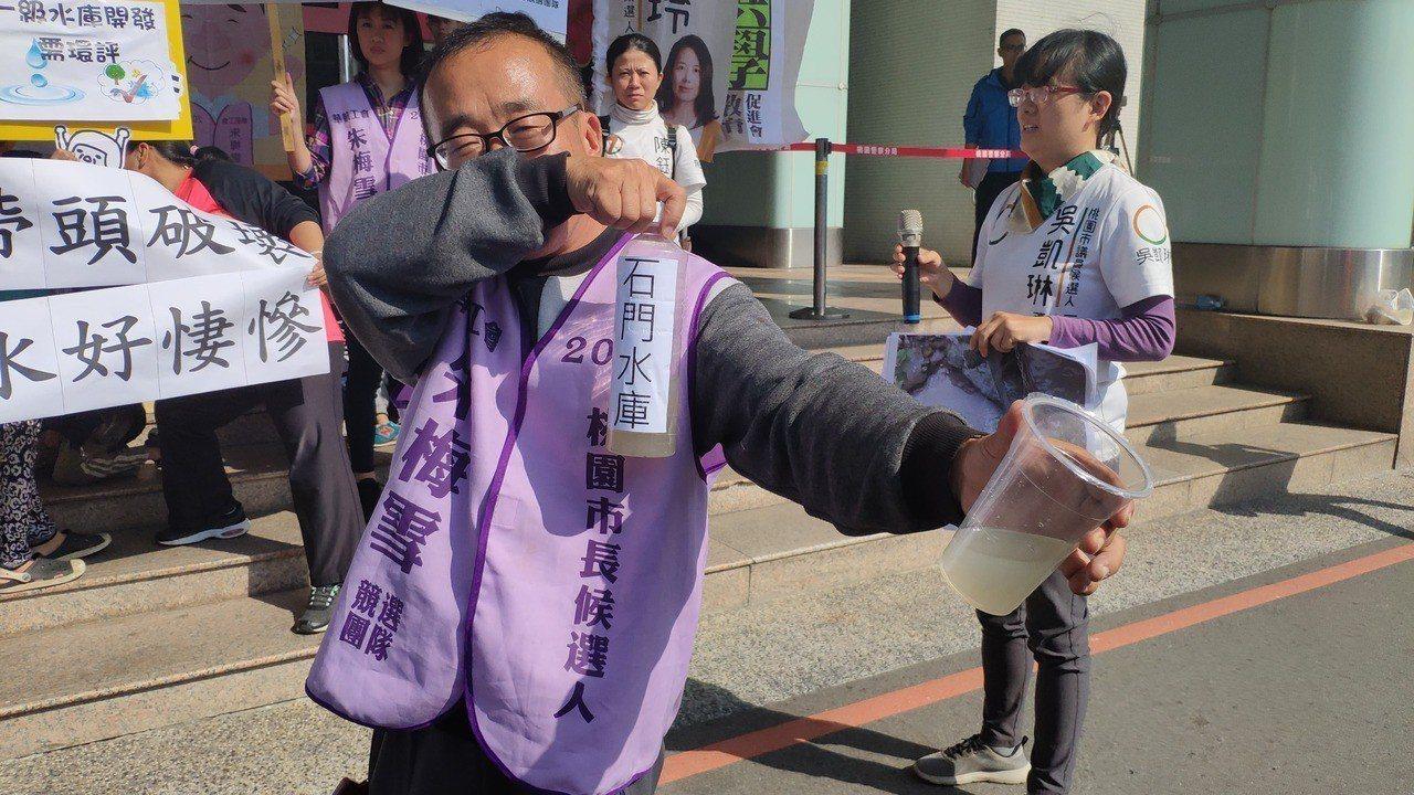 桃園市長候選人朱梅雪將石門水庫的水倒在杯中,飄出濃濃臭味。記者李京昇/攝影