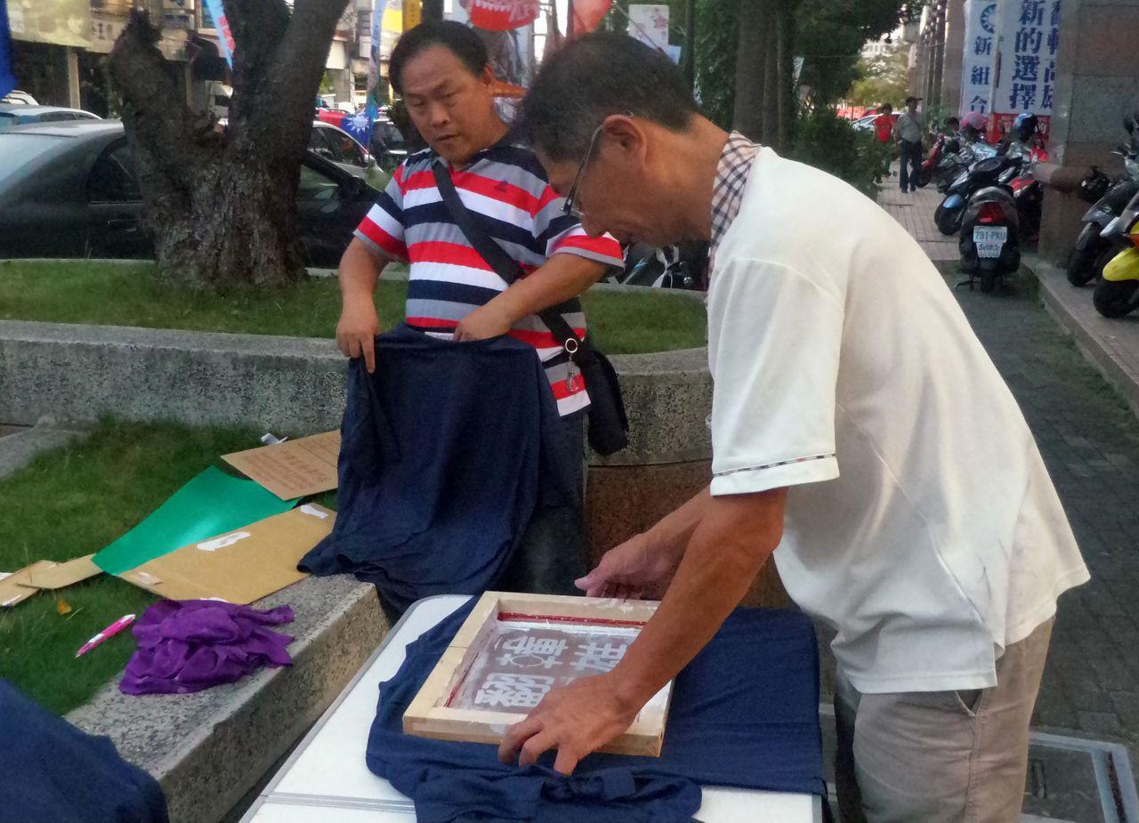 梁姓成衣老闆貨被掃光,就在路旁現製「翻轉高雄」T恤。記者林保光/攝影