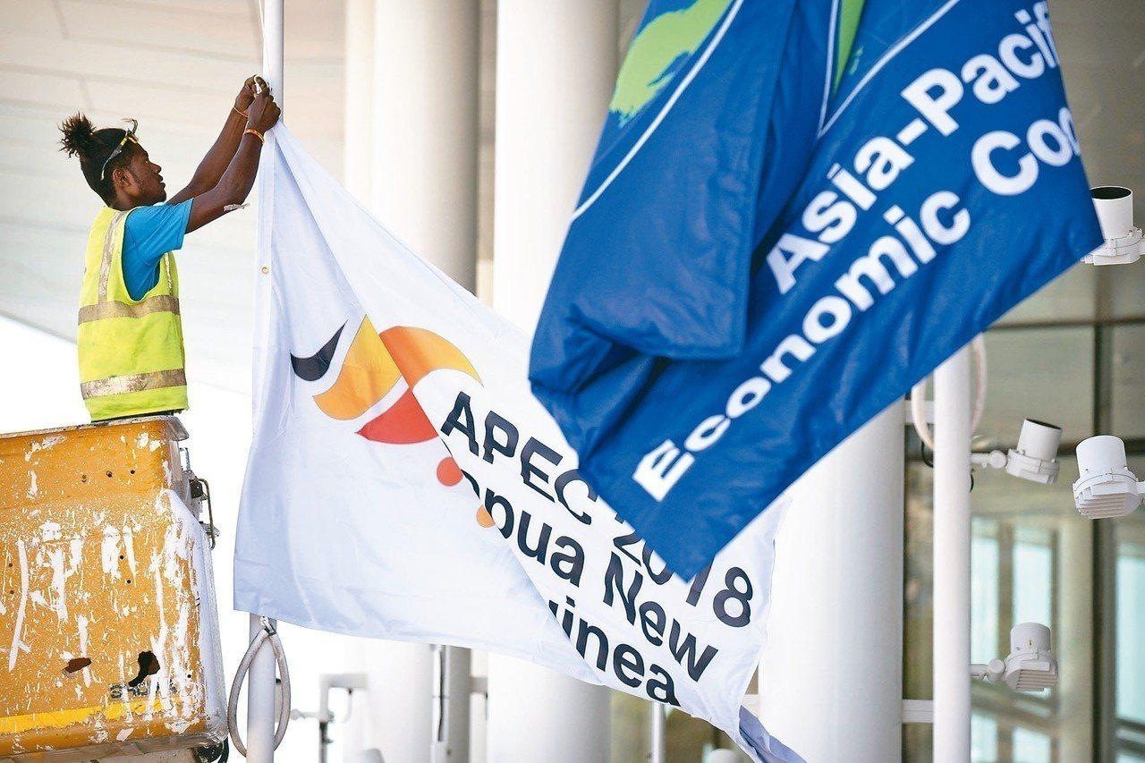 亞太經合會在巴布亞紐幾內亞首都莫士比港舉行,一名工作人員十四日在會場懸掛峰會旗幟...