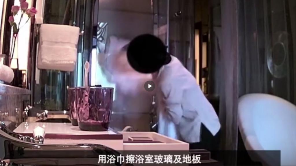 五星級酒店的清潔人員用浴巾擦拭浴室玻璃和地板。 (截自視頻)