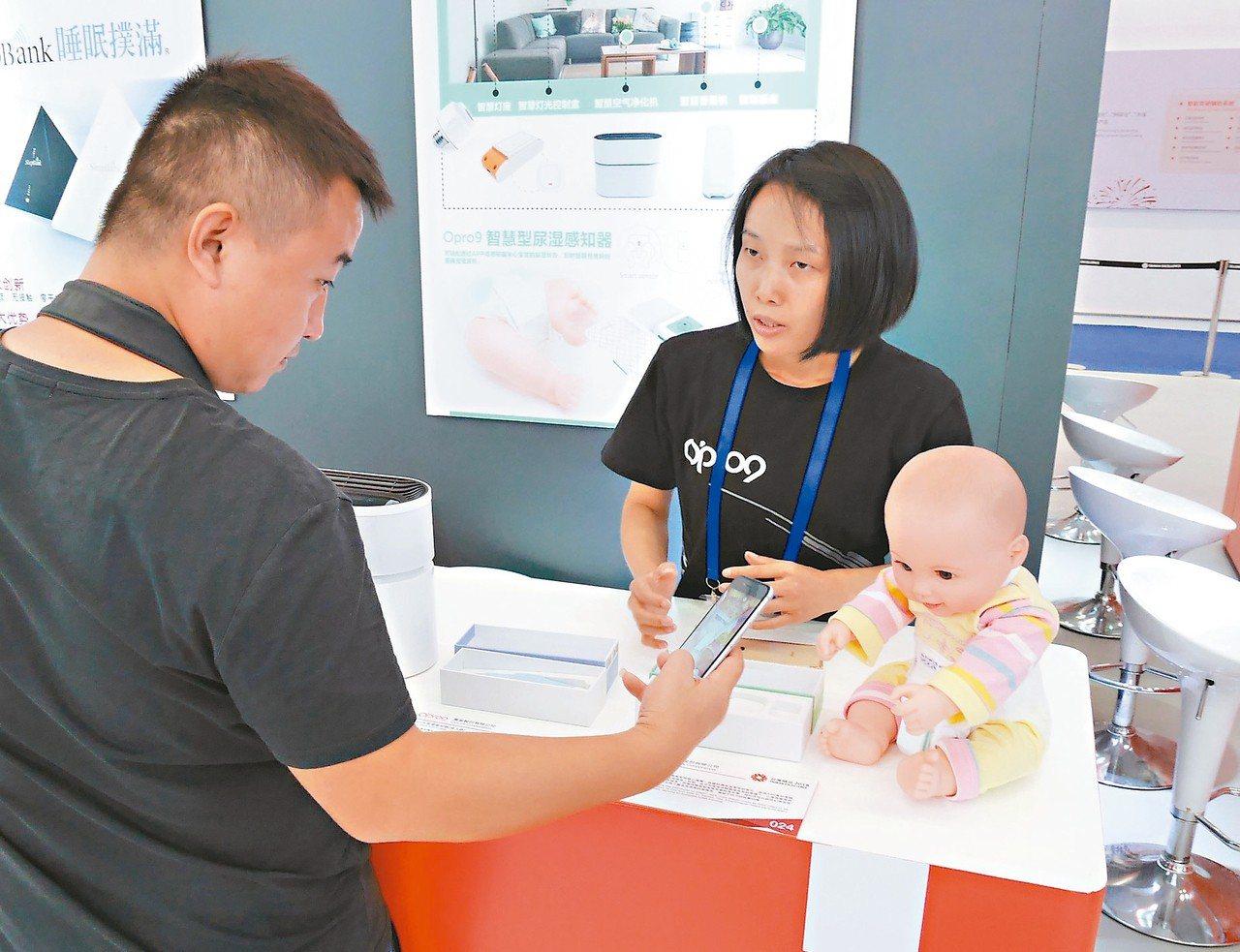 逾70件台灣科技「潮品」亮相高交會,工作人員向觀眾介紹「尿溼感知器」。 新華社