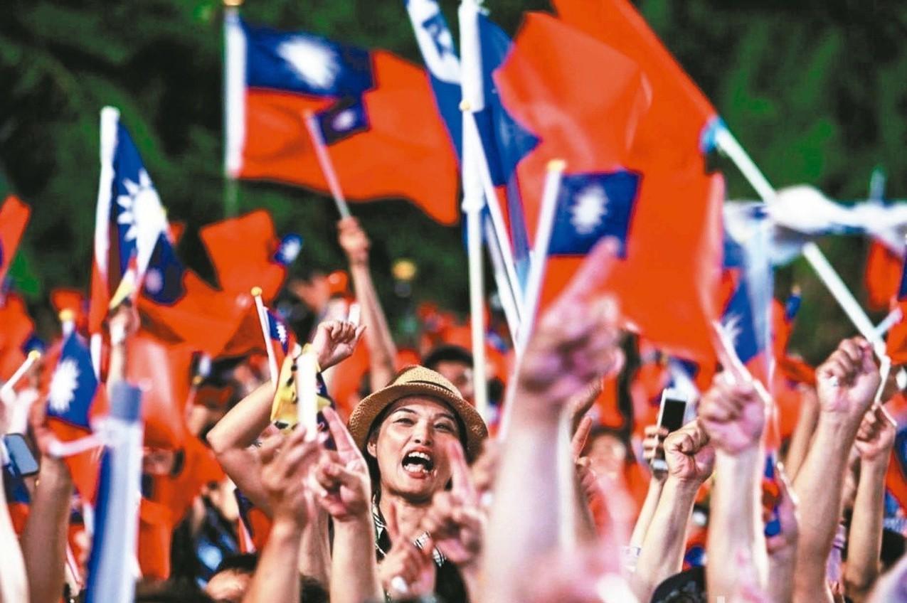國民黨高雄市長候選人韓國瑜在岡山舉辦造勢晚會,現場群眾手揮國旗比出一號手勢表達支...