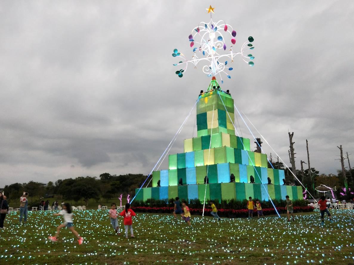 宜蘭聖誕燈飾點燈第一天,小朋友們在裝置藝術「奇幻聖誕樹」周圍追逐嘻笑玩耍。記者江...