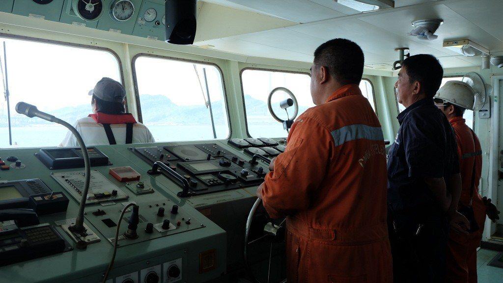 引水人(前著救生衣者)下達泊港指令,船上的舵工和三副(後者)聽令執行。圖/聯合報...